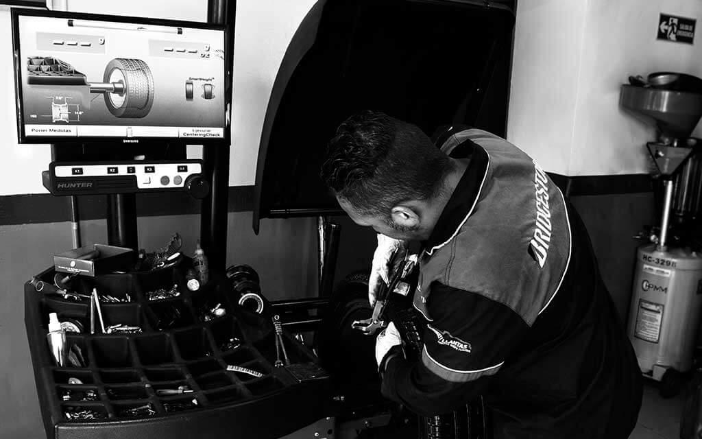 Hombre realizando balanceo de vehículo en máquina con computador